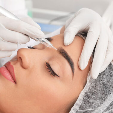 Young woman undergoing procedure of permanent eyebrow makeup in tattoo salon, closeup